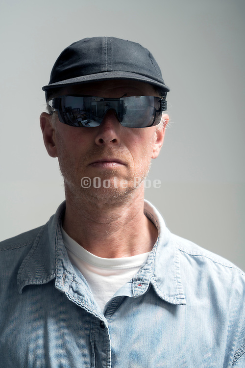 portrait of an adult male person wearing oversized sunglasses over his glasses