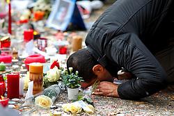 © Licensed to London News Pictures. 16/11/2015. Paris, France. A man praying at a memorial outside Bataclan Cafe in Paris, France following the Paris terror attacks on Monday, 16 November 2015. Photo credit: Tolga Akmen/LNP