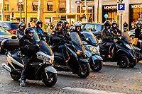 Motorscooters stopped at a traffic light on the Champs Elysees, Paris, France.