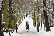 People walk across snow-covered Hampstead Heath, London, United Kingdom