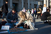 A man makes rings on teh spot outside the National Gallery and offers them for free. A women looks through his collection after she has offered him a small donation in return. The sqaure outsid ethe National Gallery is busy in the spring sun.
