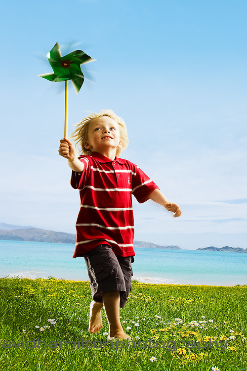 Boy at beach with wind mill