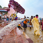A worker cleans the stone steps leading into the Ganges River while devout Hindus bathe at Dr. Rajendra Prasad Ghat, Varanasi, Uttar Pradesh, India.