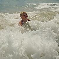 A boy plays in surf on beach.