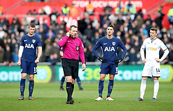 Referee Kevin Friend (second from left) waits for the Video Assistant Referee (VAR) system to rule if the goal from Tottenham Hotspur's Son Heung-Min (not in shot) is ruled offside during the Emirates FA Cup, quarter final match at the Liberty Stadium, Swansea.