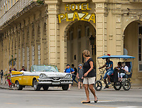 Havana, Cuba - A taxi and a bicycle taxi pass in front of Hotel Plaza near Parque Central. Classic American cars from the 1950s, imported before the U.S. embargo, are commonly used as taxis in Havana.