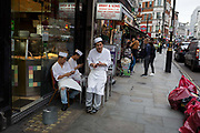 Three Chinese chefs rest outside their fast food restaurant check their messages in central London on 28th June 2017, in London, England.