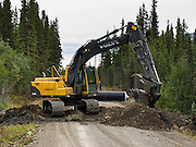 A backhoe digger gouges a culvert ditch on the McCarthy Road in Wrangell-St. Elias National Park and Preserve, Alaska, USA.