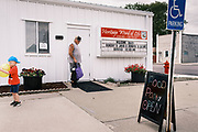 "16 SEPTEMBER 2020 - MITCHELLVILLE, IOWA: A man and his son leave the pantry at the Heritage Word of Life Church. There is no grocery store in Mitchellville, a small community in eastern Polk County. It doesn't qualify as a ""food desert"" under USDA guidelines because there are grocery stores within 10 miles in neighboring communities, but based on state data, Mitchellville is the poorest community in Polk County (which includes the Des Moines metropolitan area). The Mitchellville zip code has the lowest per capita income in Polk County. Many people don't own cars and can't get to neighboring communities to buy groceries. Every day someone from the Mitchellville library picks up hot meals from a nearby town and distributes them in the library. Heritage Word of Life, a church across the street from Library, has a food pantry in their Fellowship Room where people can pick up fresh vegetables, staples, and hygiene needs.     PHOTO BY JACK KURTZ"