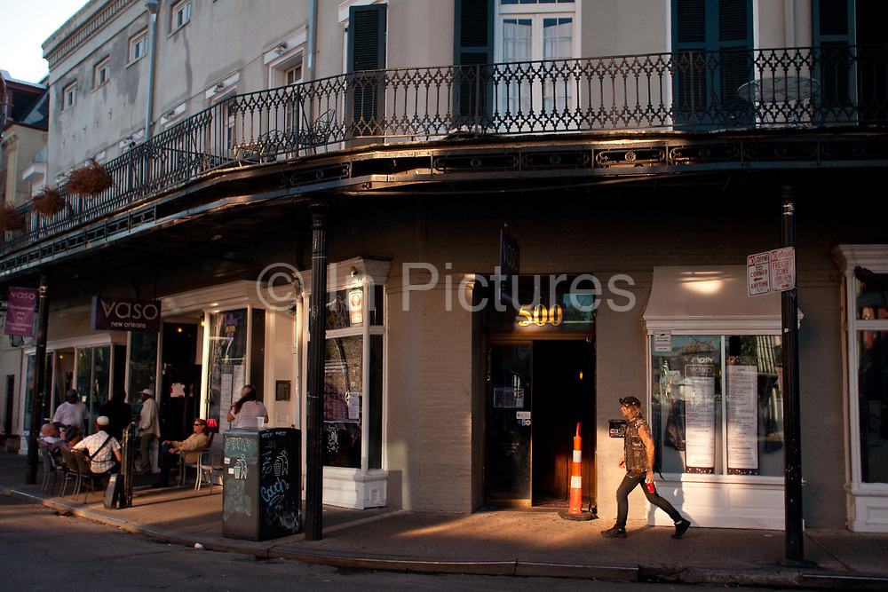 A punk man walks down Frenchman street in the afternoon light, past jazz venues, New Orleans, Louisiana, USA.