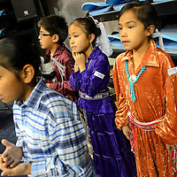 """012214  Adron Gardner/Independent<br /> <br /> Tsehootsooi Primary Learning Center second-grade student Atarah Damon, center, clasps her hands to her chin while listening to the a song performed by the Sheka family for the opening of the Bee Hółdzil """"Stronghold"""" Fighting Scouts Event Center in Fort Defiance Wednesday."""