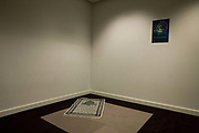 "An Islamic prayer mat has been left positioned into the corner of this seemingly ordinary room but which is a Multi-faith room for passengers seeking solace and tranquillity in an otherwise busy Terminal 5 at Heathrow Airport. Airport operator BAA provide this sanctuary in various locations around the vast airport complex but this is the newest in Departures of T5. The rug has an image from Mecca and points Eastwards to the birthplace of Mohammed and the direction of the Hajj. On the wall is a poster offering welcome to other religions: To Sikhs, Buddhists, Christians, Jews, Humanists, Jains, Hindus and Rastafarians, to name a few. From writer Alain de Botton's book project ""A Week at the Airport: A Heathrow Diary"" (2009)."