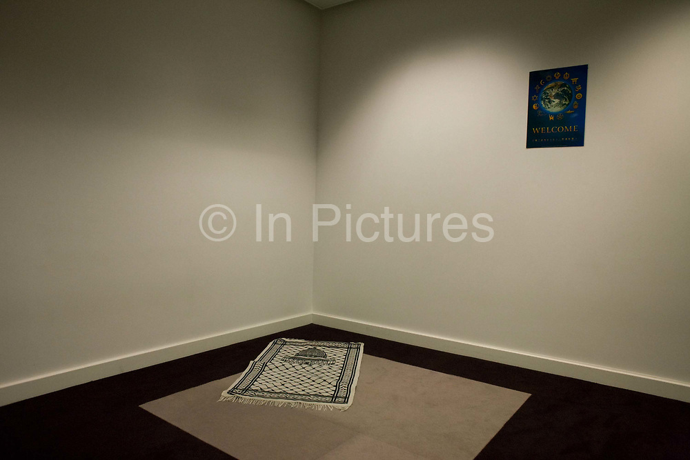 """An Islamic prayer mat has been left positioned into the corner of this seemingly ordinary room but which is a Multi-faith room for passengers seeking solace and tranquillity in an otherwise busy Terminal 5 at Heathrow Airport. Airport operator BAA provide this sanctuary in various locations around the vast airport complex but this is the newest in Departures of T5. The rug has an image from Mecca and points Eastwards to the birthplace of Mohammed and the direction of the Hajj. On the wall is a poster offering welcome to other religions: To Sikhs, Buddhists, Christians, Jews, Humanists, Jains, Hindus and Rastafarians, to name a few. From writer Alain de Botton's book project """"A Week at the Airport: A Heathrow Diary"""" (2009)."""