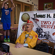 Navajo Code Talker Thomas H. Begay sings the Marines' Hymn, July 13, 2019, at Furr's Buffet Fresh, Albuquerque, New Mexico. Holding the banner is Begay's grandson, Ronald Thomas H. Begay (age 11).