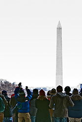 Crowd watching inauguration of Barack Obama from front steps of Lincoln Memorial, with Washington Monument in background, Washington D.C., USA.