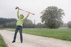 Senior woman stretching before Nordic walk with hiking poles, Bavaria, Germany