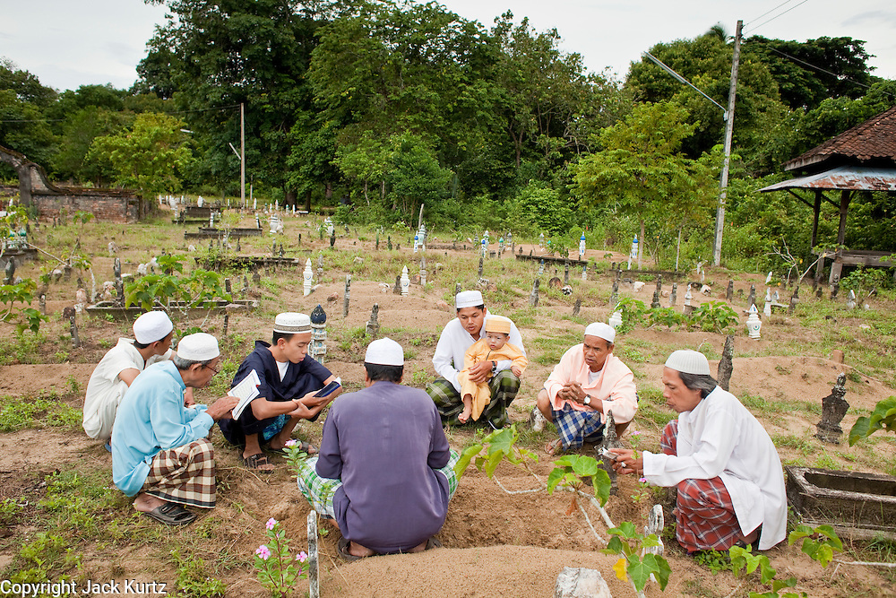 """Sept. 27, 2009 -- PATTANI, THAILAND: Thai Muslim men pray over the graves of family members in the Perkuboran To'Ayah Cemetery in Pattani, Thailand. Thailand's three southern most provinces; Yala, Pattani and Narathiwat are often called """"restive"""" and a decades long Muslim insurgency has gained traction recently. Nearly 4,000 people have been killed since 2004. The three southern provinces are under emergency control and there are more than 60,000 Thai military, police and paramilitary militia forces trying to keep the peace battling insurgents who favor car bombs and assassination.   Photo by Jack Kurtz / ZUMA Press"""