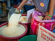 "13 FEBRUARY 2014 - BANGKOK, THAILAND: A market vendor sets up a display of rice in Khlong Toei Market in Bangkok. The Thai government instituted a ""rice pledging scheme"" after the election in 2011. The government agreed to buy farmers' rice crops at above market prices then planned to warehouse the rice and sell it on international markets when prices recovered. At the same time, India and Vietnam started to export large quantities of rice and the Thai government fell short of funds to pay for rice it had already purchased from farmers. Many farmers have not been paid for rice grown in 2013 and some of the rice in the Thai warehouses is allegedly rotting. Thailand has fallen from number 1 rice exporter in the world to number 3 and several government to government contracts the Thais signed with rice importing countries (like China) have been cancelled. Farmers, once key supporters of the government are now joining anti-government protests in Bangkok and occupying government ministries including the Ministry of Commerce.    PHOTO BY JACK KURTZ"