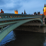 Tourists walk along Westminster Bridge at dusk, with Big Ben and the Palace of Westminster in the background.