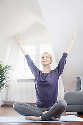Young woman doing yoga on exercise mat in living room, Bavaria, Germany