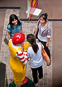 04 MAY 2010 - BANGKOK, THAILAND: Women talk to each other in front of a Ronald McDonald at a McDonald's restaurant on Chong Nonsi Road in Bangkok, Thailand. American fast food chains, like McDonald's, have done extremely well in Thailand.  PHOTO BY JACK KURTZ