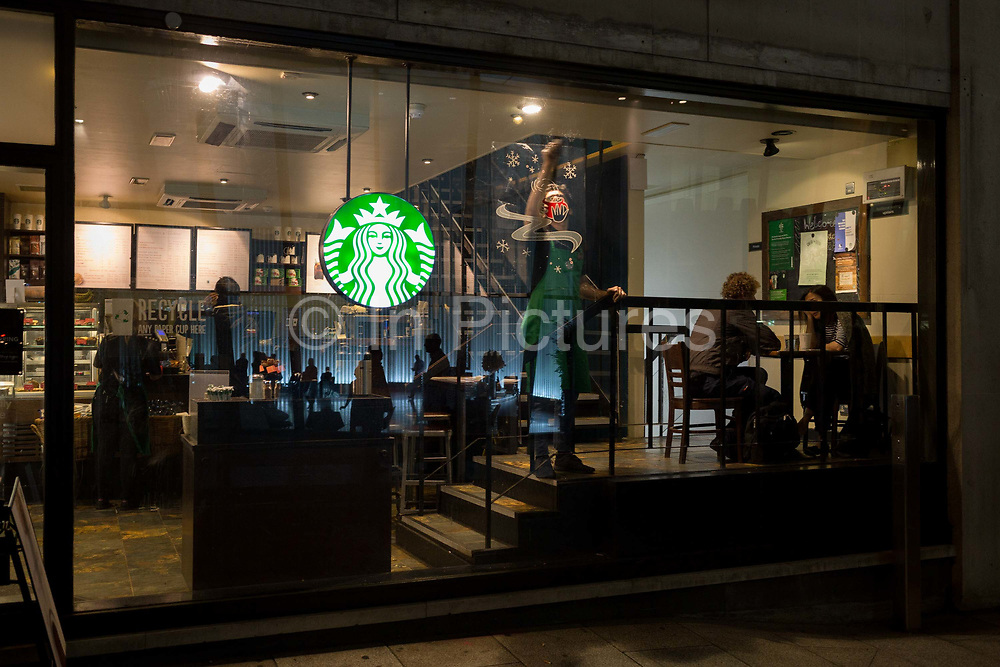 As customers talk, a Starbucks employee places a Christmas poster to the window of a coffee shop on Walbrook in the heart of the Square Mile, the capitals historical and financial centre, on 1st November 2017, in the City of London, England.