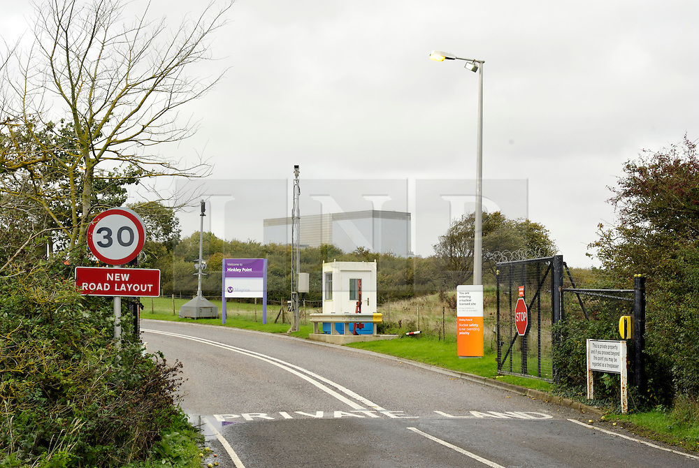 © Licensed to London News Pictures. 21/10/2013.  Hinkley Point, Somerset, UK.  Hinkley B and main gate, Hinkley Point Nuclear Power Station, which currently comprises the decommissioned Hinkley A station with Magnox Reactors (blue square buildings) and Hinkley B station (grey building complex, a more modern AGR design). The UK Government today announced the go-ahead for a new nuclear power station at Hinkley Point C in Somerset, to be built by a consortium with French firm EDF Energy and Chinese investment for the first time in UK nuclear power generation.21October 2013.<br /> Photo credit : Simon Chapman/LNP