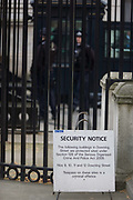 Security notice sign detailing the laws protecting Downing Street, the Prime Minister's address in Westminster London. Section 128 of the Serious Organised Crime and Police Act 2005 restricts those gaining access to this and other protected site. Barriers have been there since 1920 but in 1982 access was more fully restricted with railings and a demountable gate. This was replaced by the current black steel gates in 1989. The increase in security was again due to an increase in violence, particularly by the IRA but otherwise to street protests such as the Poll Tax riot in 1990.
