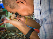 06 JANUARY 2013 - BANGKOK, THAILAND:  A man uses a loupe to inspect an amulet while shopping in the amulet market in Bangkok. Hundreds of vendors sell amulets and Buddhist religious paraphernalia to people in the area north of the Grand Palace near Wat Maharat in Bangkok.   PHOTO BY JACK KURTZ
