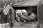 A soldier waves the an American flag after returning home form war.