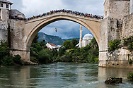 A crowd watches as a man leaps off the Stari Most, 79 feet (24 meters) above the Neretva River in Mostar, Bosnia and Herzegovina. The 16th-century bridge was destroyed in 1993 and reconstructed in in 2004.