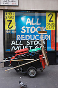 Street sweeper's cart and brush in front of outdoor shop's end of business sale where all stock is reduced and must go.