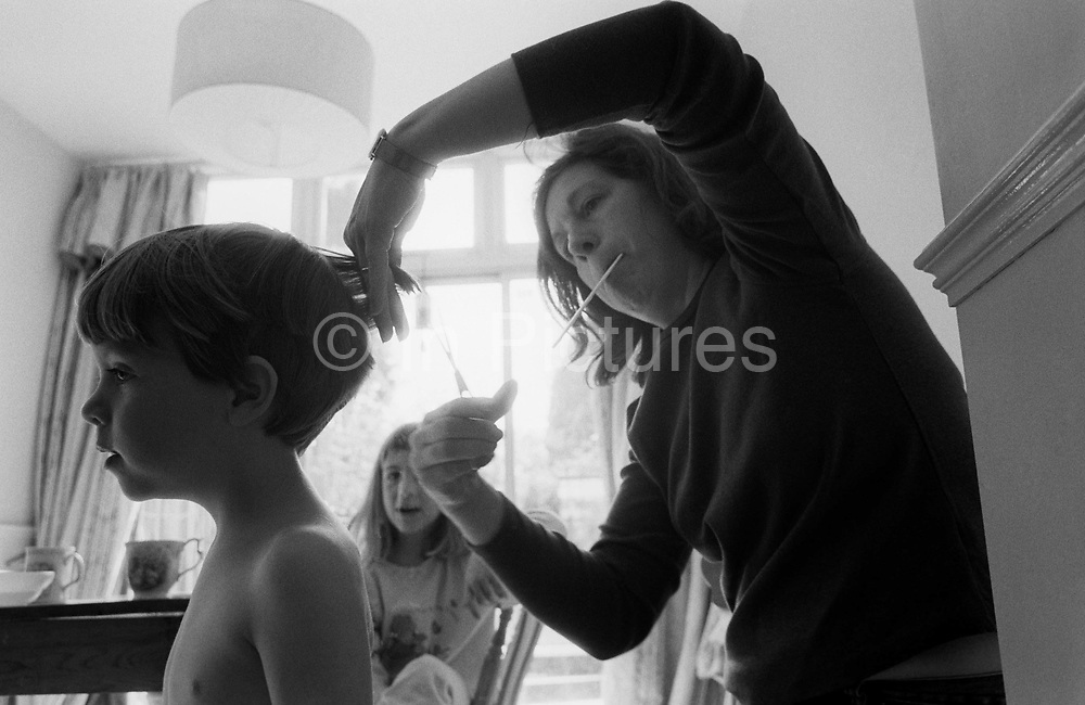 """A young three year-old boy has his hair cut by his mother in the family South London home. Lifting his hair with her fingers, the mum snips with a pair of scissors. While lifting her left elbow to gain the right angle of her cutting, we see her holding a comb in her mouth. The boy's elder sister looks on offering unhelpful comments which will eventually lead to an exchange of unkind words between the siblings while their mother concentrates hard on not making a mess of the kid's haircut. From a personal documentary project entitled """"Next of Kin"""" about the photographer's two children's early years spent in parallel universes. Model released."""