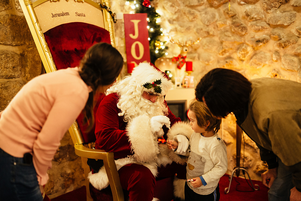 Issa Kassissieh dressed as Santa Claus, hands candies to a child, at Santa's House in the Old City of Jerusalem, Israel, on December 19, 2018, before it opens for visitors. Issa Kassissieh, a Christian Arab living in the Old City's Christian Quarter is thought to be Jerusalem's only Santa Claus. He has turned the first floor of his 700-year-old house into Santa's House. He has been doing it for a number of years unofficially, and in July was fully ordained as Santa Claus at a conference in Copenhagen and has even been to Santa school in Denver and Michigan. According to him, he is the only one in Israel and perhaps even in the middle east.
