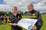 Brian Brady, who won €2500 in the Allianz predictions competition, presents the cheque to Ger Collins (bald), chairman of Naomh Moninne Hurling club in Dundalk.