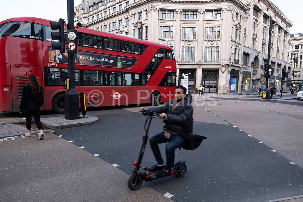 Man passes on an e-scooter Oxford Street at Oxford Circus empty of shoppers as the national coronavirus lockdown three continues on 28th January 2021 in London, United Kingdom. Following the surge in cases over the Winter including a new UK variant of Covid-19, this nationwide lockdown advises all citizens to follow the message to stay at home, protect the NHS and save lives.