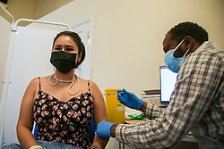 © Licensed to London News Pictures. 25/06/2021. London, UK. Vaccinator Ahmed Said administers the first dose of the Pfizer Covid-19 vaccine to Naphapa Ewington in Tottenham, north London. Londoners are urged to get Covid-19 vaccine this weekend. Photo credit: Dinendra Haria/LNP