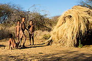 A group of young naked Bushmen children playing near their huts. Photographed in Namibia