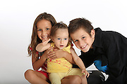 Three smiling young siblings