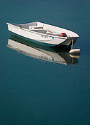 A single small boat floats quietly in the shallow waters of a cove on the coast of Maine.