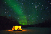 In an illuminated tent, two campers toast to the aurora borealis by celebrating with a bottle of wine in the far north of Alaska, Alaska,USA