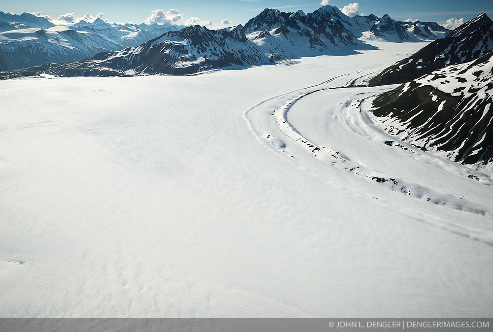 The upper regions of the Tsirku and Buckwell Glaciers start in Tatshenshini-Alsek Provincial Park. The Tsirku Glacier (foreground) flows downward to become the Tsirku River, near Haines, Alaska and the Buckwell Glacier (upper right) flows to become Michael Creek which shortly connects with the O'Connor River. Tatshenshini-Alsek Provincial Park is located in the very northwestern corner of British Columbia, Canada. The park sits between Kluane National Park and Reserve in the Yukon and Glacier Bay and Wrangell-St. Elias National Parks and Preserves in Alaska. All together, they form the largest protected area in thew world, approximately 21 million acres. The Tatshenshini and Alsek Rivers are protected in their entirety making them the only large watershed in North America that is totally protected.<br /> <br /> The remote park is known for its spectacular glacier and icefields, rafting and kayaking, hiking and mountaineering. Tatshenshini-Alsek Provincial Park is home to grizzly bears, Dall's sheep, wolves, mountain goats, moose, eagles, falcons, and trumpeter swans.<br /> <br /> The park was designated a UNESCO World Heritage site in 1994.