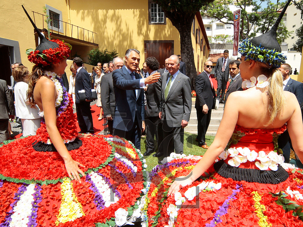 Portugal, FUNCHAL : Spanish King Juan Carlos (R) and Portugal's President Anibal Cavaco Silva (L) are hosted by women wearing dresses made out of flowers during their visit to the Madeira Wine Institute in Funchal on the Atlantic island of Madeira July 31, 2009, on the second of a three-day official visit of the Spanish monarchs.  PHOTO/ GREGORIO CUNHA