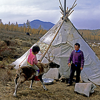 """MONGOLIA, Youngster of the Tsataan (""""reindeer people"""") learns to ride under watchful eye of his grandfather."""