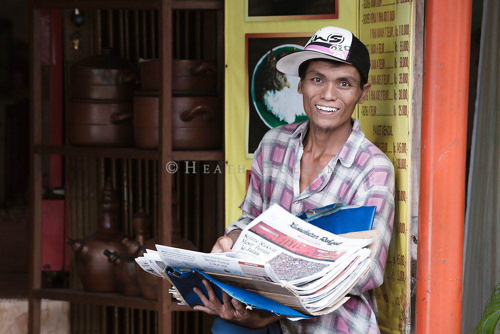 Young male selling newspaper beside the road in Yogyakarta.