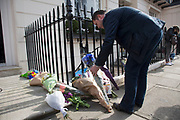 "London, UK. Monday 8th April 2013. A member of the public brings flowers to the London residence on Chester Square of Baroness Margaret Thatcher following the announcement of her death. Maggie Thatcher (87), aka the ""Iron Lady"" dominated British politics for 20 years, died peacefully on 8/4/13 following a stroke."