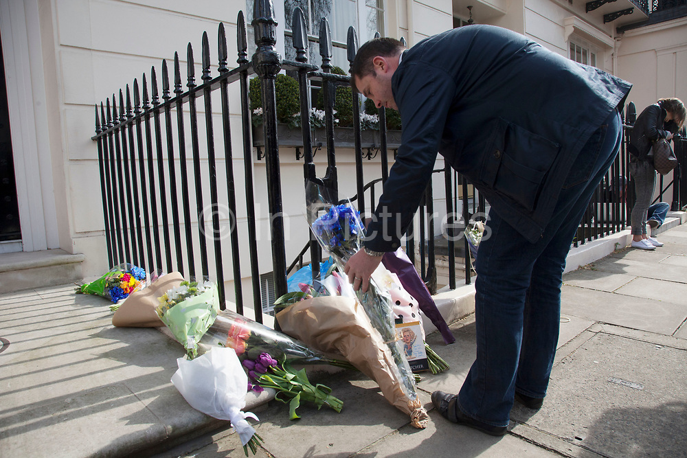 """London, UK. Monday 8th April 2013. A member of the public brings flowers to the London residence on Chester Square of Baroness Margaret Thatcher following the announcement of her death. Maggie Thatcher (87), aka the """"Iron Lady"""" dominated British politics for 20 years, died peacefully on 8/4/13 following a stroke."""