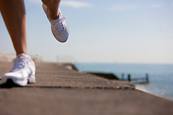Close up of a woman's legs running by waterfront