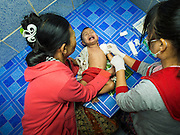05 MARCH 2014 - MAE SOT, TAK, THAILAND: A woman comforts her child while medics examine him after his surgery for an abscessed sore at the Mae Tao Clinic. The Mae Tao Clinic provides  healthcare to over 150,000 displaced Burmese per year and is the leading healthcare provider for Burmese along the Thai-Myanmar border. Reforms in Myanmar have alllowed NGOs to operate in Myanmar, as a result many NGOs are shifting resources to operations to Myanmar, leaving Burmese migrants and refugees in Thailand vulnerable.     PHOTO BY JACK KURTZ
