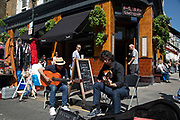 Buskers playing guitar on Portobello Road Market in Notting Hill, West London, England, United Kingdom. People enjoying a sunny day out hanging out at the famous Sunday market, when the antique stalls line the street.  Portobello Market is the worlds largest antiques market with over 1,000 dealers selling every kind of antique and collectible. Visitors flock from all over the world to walk along one of Londons best loved streets.